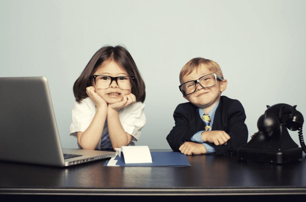deux enfants déguisés en business people derrière un bureau