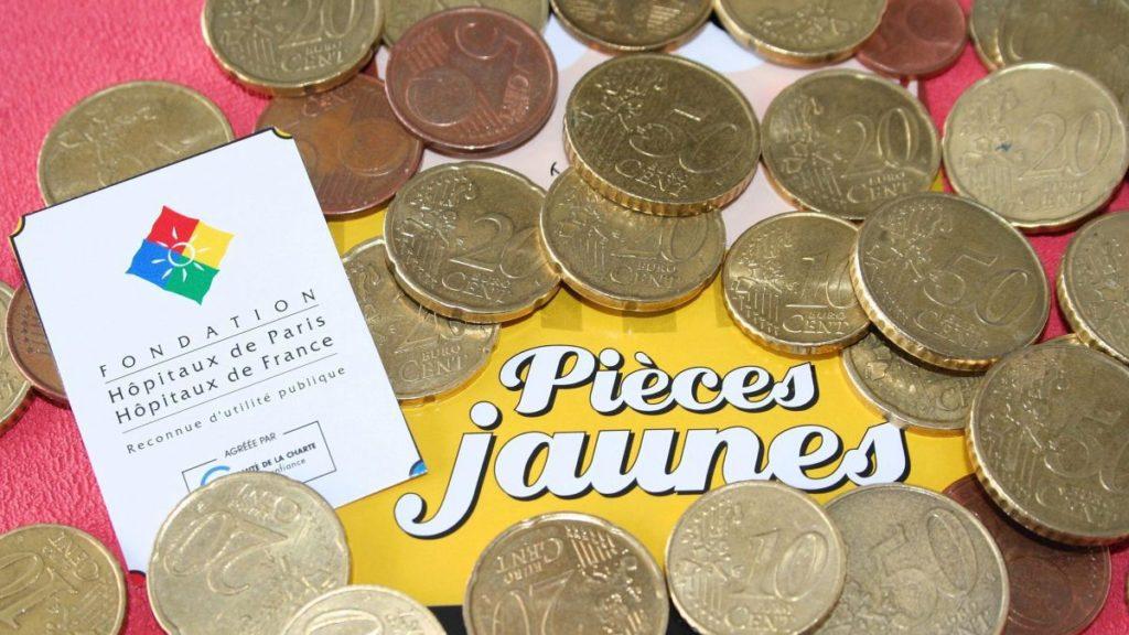 pieces jaunes sur une table avec une carte des hopitaux de France